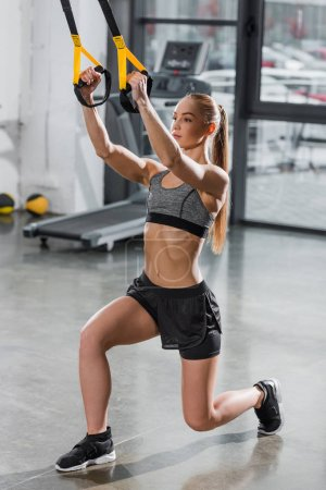 attractive athletic sportswoman working out with suspension straps in gym