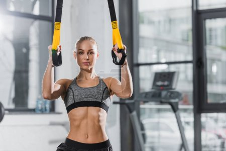 attractive athletic sportswoman working out with suspension straps in gym and looking at camera