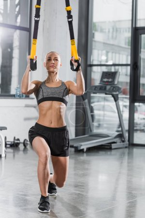 attractive muscular sportswoman working out with suspension straps in gym