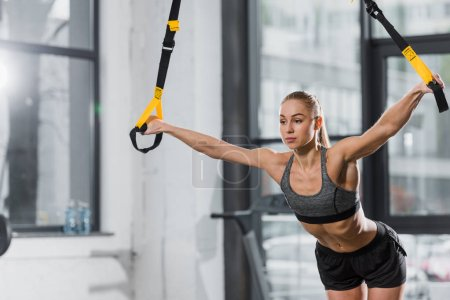 attractive athletic bodybuilder working out with suspension straps in gym