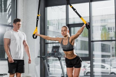 trainer looking at sportswoman exercising with suspension straps in gym