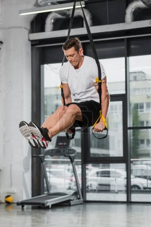 handsome athletic bodybuilder exercising with suspension straps in gym