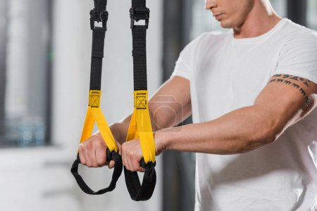 cropped image of tattooed athletic bodybuilder holding suspension straps in gym