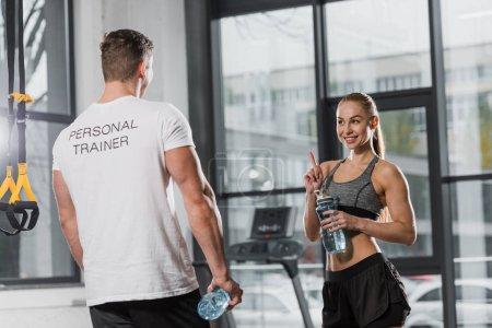 Photo pour Entraîneur et sportive tenant des bouteilles de sport avec de l'eau et se regardant dans la salle de gym - image libre de droit
