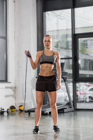 attractive athletic bodybuilder holding jumping rope in gym and looking at camera