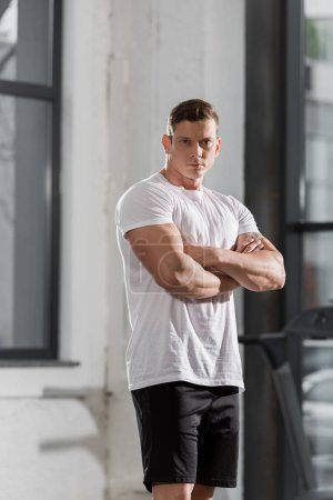 handsome athletic bodybuilder standing with crossed arms and looking at camera in gym