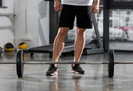 cropped image of athletic bodybuilder standing near barbell in gym