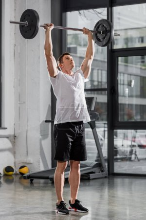 Photo for Sportive athletic bodybuilder training with barbell in gym - Royalty Free Image