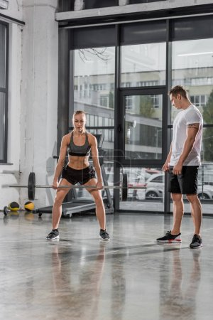 trainer watching at sportswoman exercising with barbell in gym