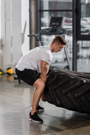 Photo for Side view of handsome muscular bodybuilder exercising with tire in gym - Royalty Free Image