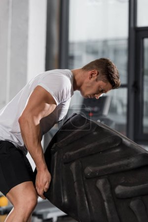 handsome athletic bodybuilder exercising with tire in gym