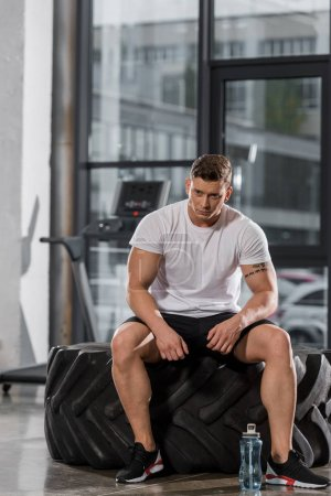 Photo for Tired handsome athletic bodybuilder sitting on tire in gym - Royalty Free Image