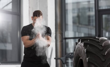 handsome athletic bodybuilder applying talcum powder before training with tire in gym