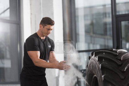 handsome muscular bodybuilder applying talcum powder before training with tire in gym