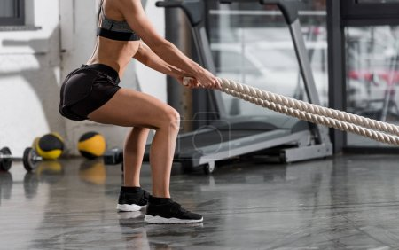 cropped image of athletic bodybuilder working out with ropes in gym