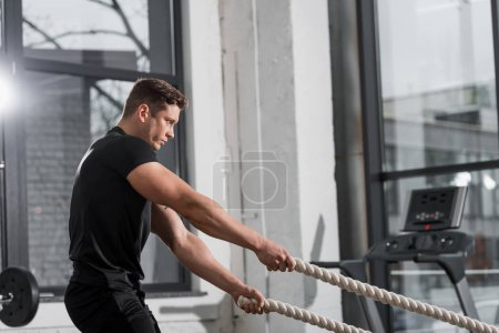 side view of handsome muscular bodybuilder working out with ropes in gym