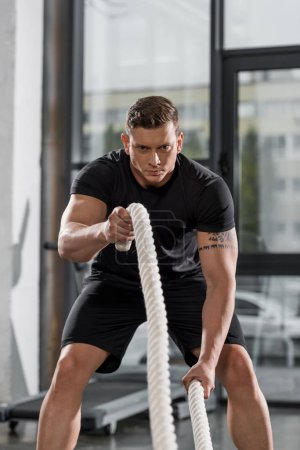 handsome muscular bodybuilder working out with ropes in gym