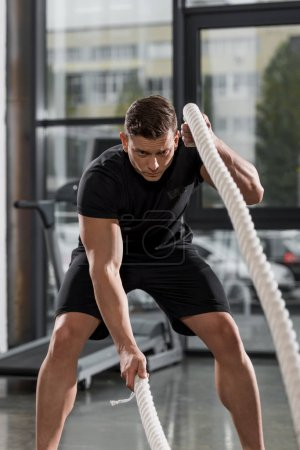 handsome sportive bodybuilder working out with ropes in gym