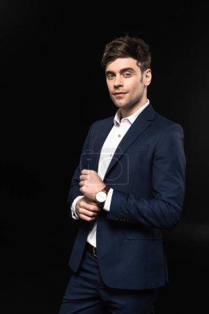 Photo pour Beau jeune homme d'affaires en costume élégant avec montre-bracelet en regardant la caméra isolée sur fond noir - image libre de droit