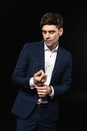 handsome young businessman buttoning cuffs on sleeve isolated on black