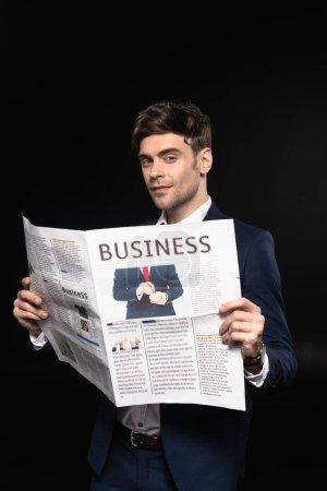 attractive young businessman with newspaper looking at camera isolated on black