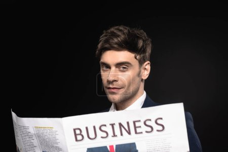 Photo for Close-up portrait of handsome young businessman with newspaper looking at camera isolated on black - Royalty Free Image