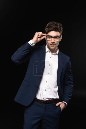 handsome young businessman in stylish suit and eyeglasses looking at camera isolated on black