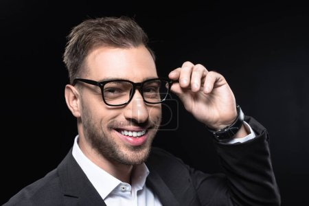 close-up portrait of handsome young businessman in eyeglasses looking at camera isolated on black