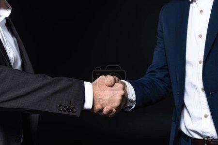 Photo pour Plan recadré d'hommes d'affaires serrant la main isolés sur noir - image libre de droit