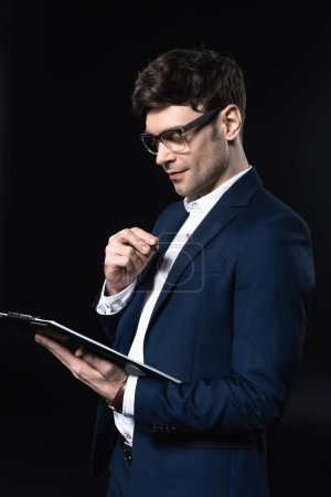 handsome young businessman with clipboard isolated on black