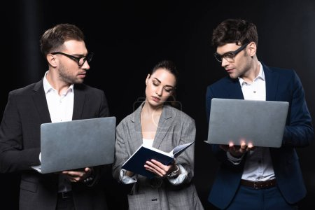 group of confident business people working together with laptops and notebook isolated on black
