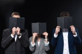 group of business people covering faces with notebooks isolated on black