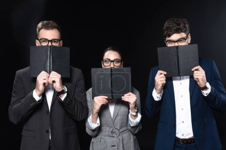 group of business people covering faces with notebooks and looking at camera isolated on black