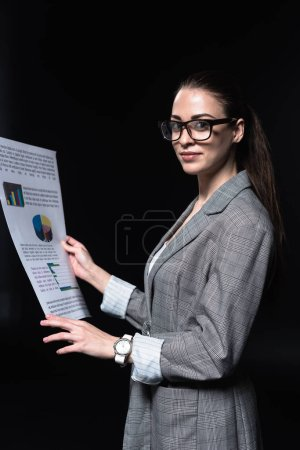 beautiful young businesswoman in stylish jacket holding newspaper isolated on black