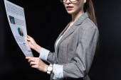 cropped shot of young businesswoman in stylish jacket holding newspaper isolated on black