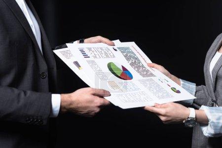 Photo pour Photo recadrée de transmettre des documents graphiques isolée sur fond noir des gens d'affaires - image libre de droit
