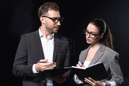 confident business people with clipboard having conversation isolated on black