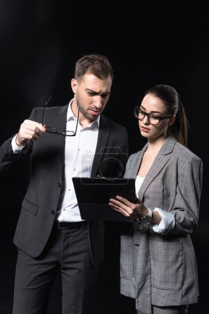 serious business people with clipboard having conversation isolated on black