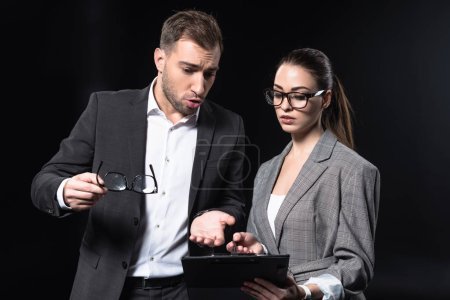 young business people with clipboard having conversation isolated on black