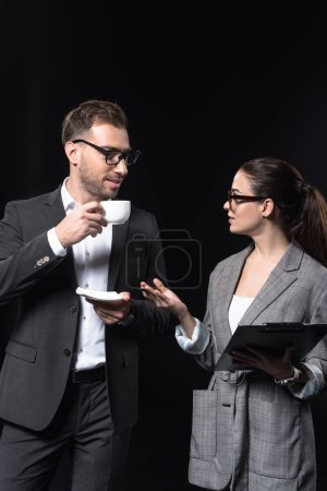 business people with cup of coffee and clipboard having conversation isolated on black