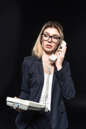 beautiful young businesswoman talking by wired phone isolated on black