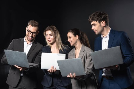 group of happy business people working with laptops together isolated on black