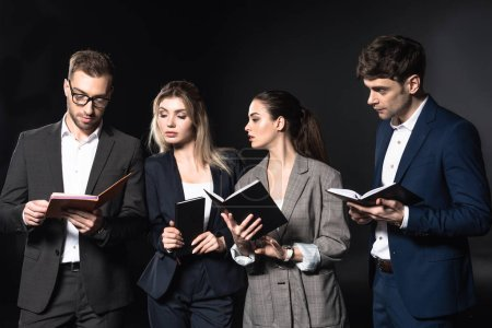 group of successful business people reading notebooks together isolated on black