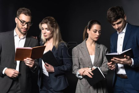 group of serious business people reading notebooks together isolated on black