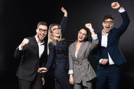 group of successful business people celebrating victory isolated on black