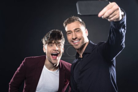 handsome young men in stylish clothes taking selfie with smartphone on black