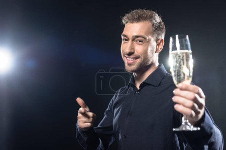 smiling young man in stylish blazer holding champagne glass and pointing at camera isolated on black
