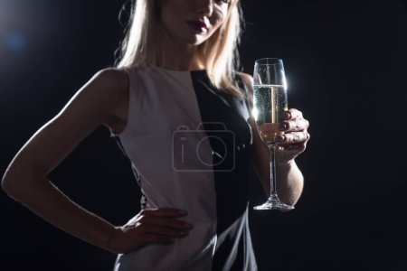 cropped shot of young woman holding glass of champagne on black