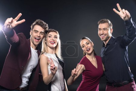 Photo for Group of happy stylish young friends looking at camera and showing peace signs together on black - Royalty Free Image