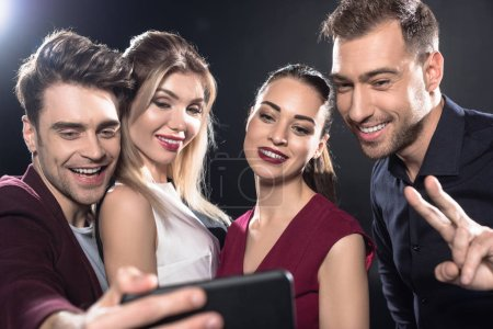 close-up shot of happy group of friends taking selfie with smartphone during party on black